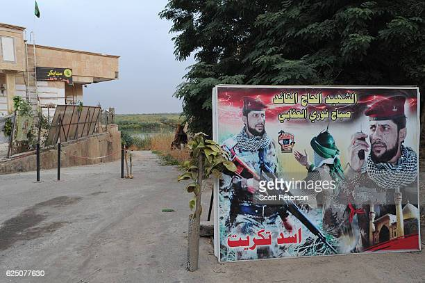 Banner marks the entrance to the memorial to the Islamic State massacre of 1,700 Shiite Air Force cadets from Camp Speicher beneath a bridge where...
