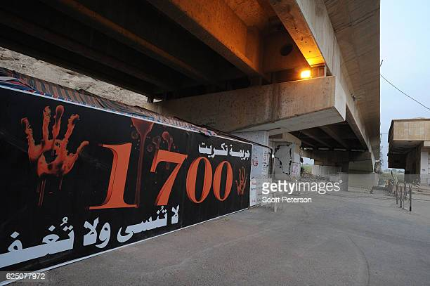 A banner marks the memorial to the Islamic State massacre of 1700 Shiite Air Force cadets from Camp Speicher beneath a bridge where victims were shot...