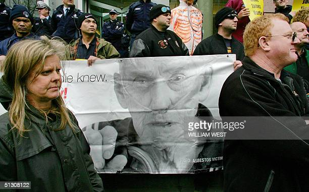 A banner of an asbestos victim is held as people listen to the speakers after some 15000 trade unionist marched through the streets of central...