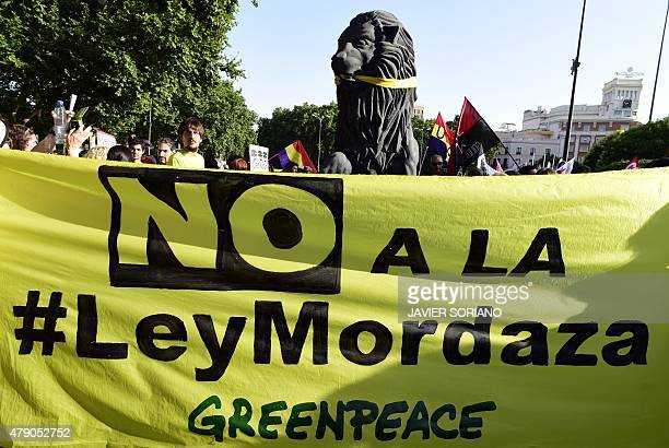 A banner of Greenpeace against the public security law 'ley mordaza' is deployed during a demonstration in Madrid on June 30 2015 The lower house of...