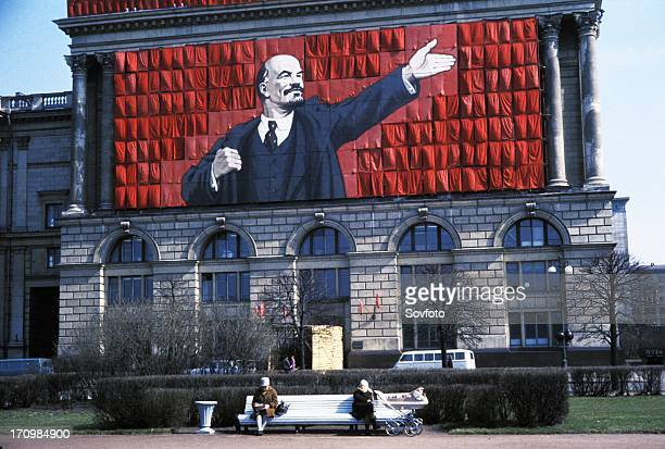 A banner of lenin on the side of a building overlooking two elderly women sitting on a park bench in leningrad ussr 1960s