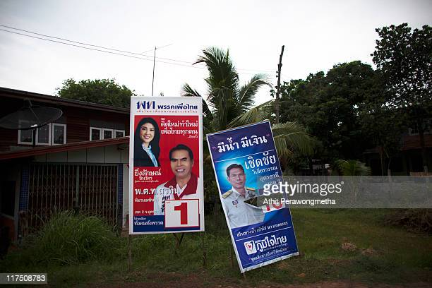 A banner of Puea Thai Party hangs next to a defaced banner of the Bhum Jai Thai Party in a village designated as a Red Shirt Village of Democracy on...
