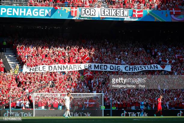 Banner of support is raised as the ball is kicked out of play in the tenth minute followed by a minute of applause in support of Denmark...