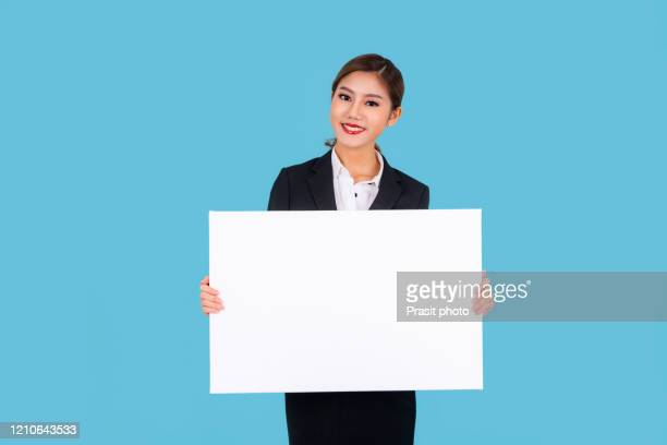 banner of young happy asian businesswoman in suit feeling happiness and holding empty white canvas frame for text or business advertising isolated on cyan background - person holding up sign stock pictures, royalty-free photos & images