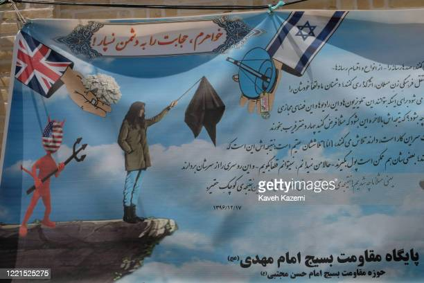 A banner posted on a wall by the Basiji group of Imam Mahdi mosque depicts an Iranian woman who has taken off her veil and is holding it on a piece...