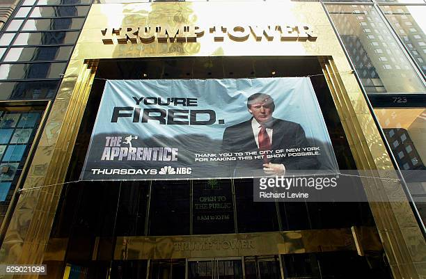 A banner promoting the hit television show The Apprentice hangs from the entrance of Trump Tower on March 19 2004 The expression You're Fired is...