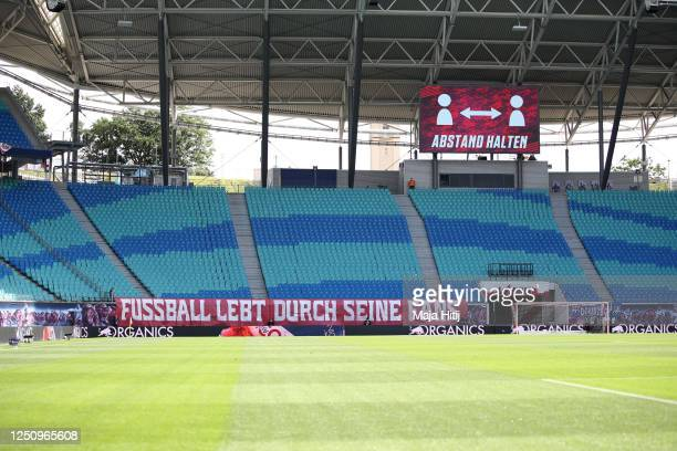 Banner reading 'Football lives through it's fans' is placed in front of empty stands ahead the Bundesliga match between RB Leipzig and Borussia...