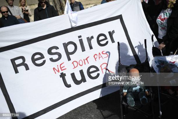 A banner reading in French breath should not kill as people gather on the Seine river banks on March 10 2018 in central Paris for a demonstration to...