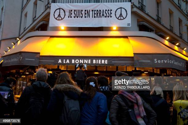 """Banner reading """"Je suis en terrasse"""" hangs above as journalists gather in front of the bar """"A la Bonne Biere"""" in Paris on December 4 during its..."""