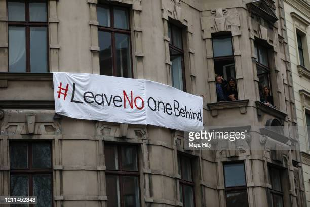 A banner reading #Leave No One Behind is hung from a building as part of a demonstration in Kreuzberg district on May Day during the novel...