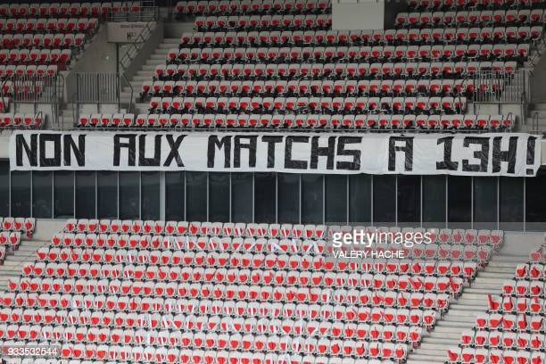 A banner reading 'no to matches broadcast at 1pm' hangs on the tribune of the Allianz Riviera Stadium in Nice ahead of the kick off of the French...