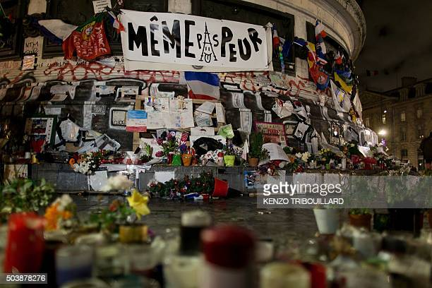 TOPSHOT A banner reading Not even afraid flowers candles drawings and notes are pictured at the bottom of the Republic monument during a ceremony in...
