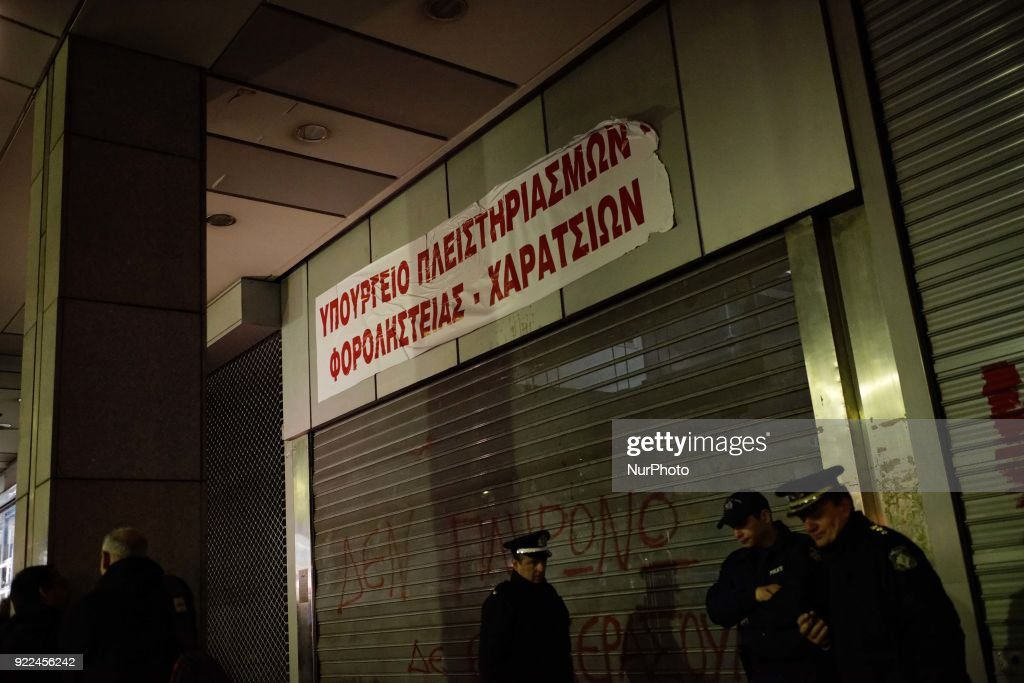 "A banner reading ""ministry of auctions and tax robbery"" is seen at the entrance of the ministry of economics during a demonstration against online auctions of foreclosed properties in Athens, Greece on February 21, 2018. A rally against online auctions of foreclosed properties was held in central Athens by labor unions affiliated to the Greek Communist Party (KKE)."