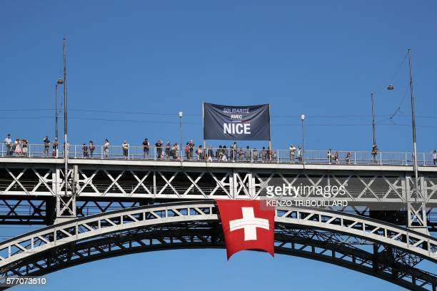 A banner reading 'Solidarite avec Nice' is displayed above a Switzerland's national flag suspended from a bridge four days after deadly attack of the...