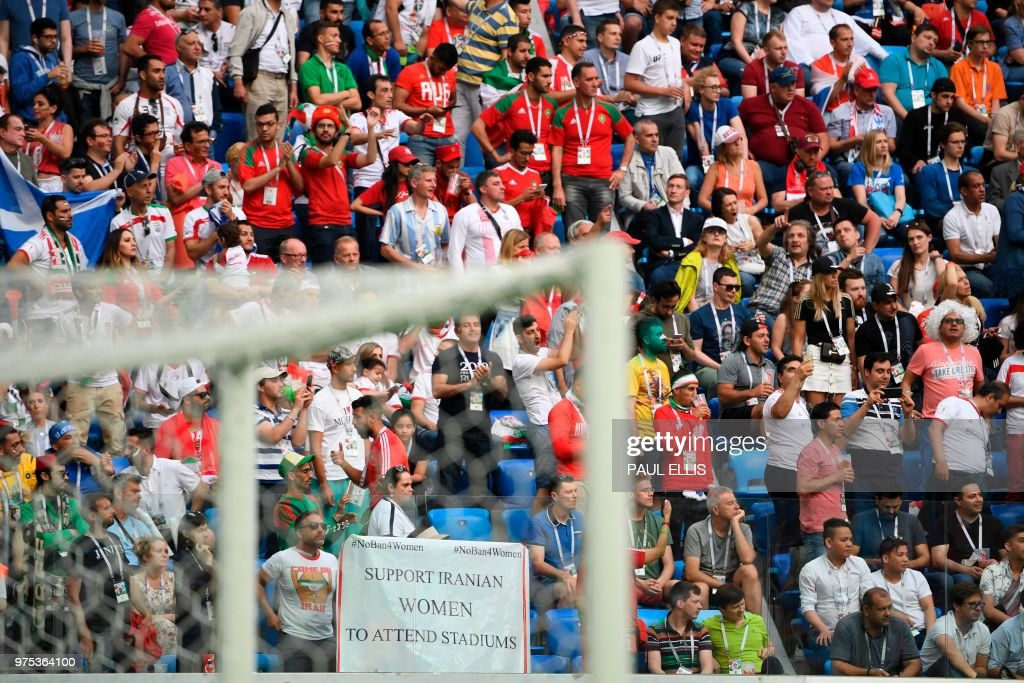 A banner reading 'Support Iranian women to attends stadiums' is displayed during the Russia 2018 World Cup Group B football match between Morocco and Iran at the Saint Petersburg Stadium in Saint Petersburg on June 15, 2018. (Photo by Paul ELLIS / AFP) / RESTRICTED