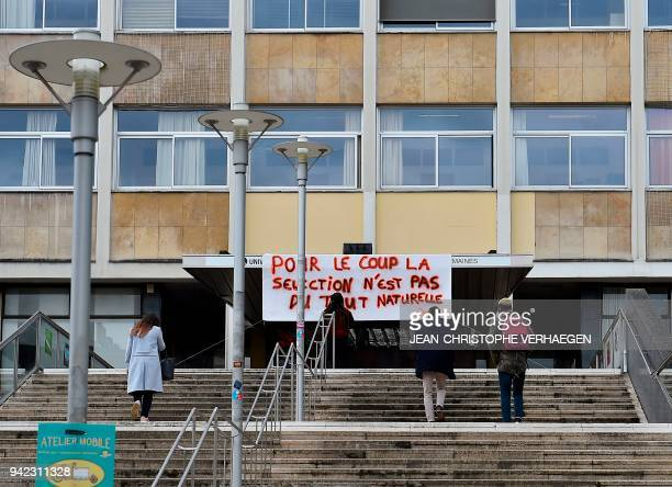 """Banner reading """"Therefore, selection appears not to be natural at all"""" is attached to the facade of the Faculty of Humanities - University of..."""
