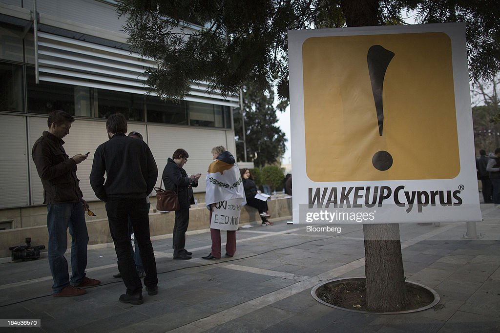 A banner reading 'Wake Up Cyprus' hangs from a tree near the Cypriot parliament in Nicosia, Cyprus, on Sunday, March 24, 2013. Cyprus's fate hangs in the balance as euro-area finance ministers meet today to decide whether the tiny Mediterranean island has done enough for a bailout that will avert its financial collapse. Photographer: Simon Dawson/Bloomberg via Getty Images