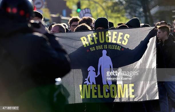 A banner reads «Refugees Welcome`is being held by a leftwing protester during annual May Day demonstrations on May 1 2015 in Hamburg Germany In...