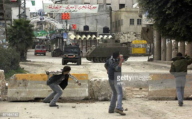 A banner reads 'The fight to liberate detainees is the mother of all battles' hangs across a streets as Palestinian youth throw stones at Israeli...