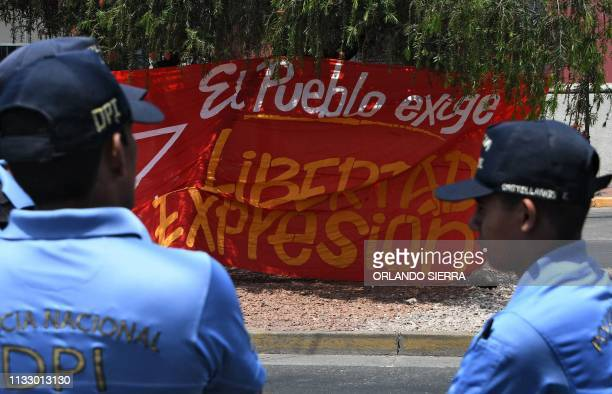 A banner reads The People Demand Freedom of Expression as members of the National Police of Investigation surround the premises of Radio Globo where...