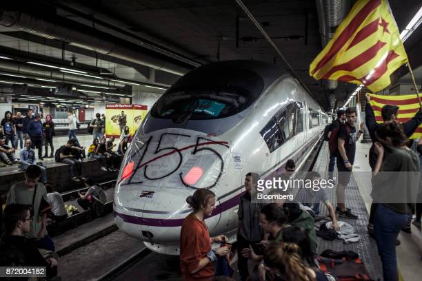 A banner referencing 'Article 155' sits on the nose of an AVE highspeed train at Barcelona Sants central station during a political demonstration...