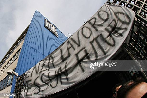 A banner set at the entrance reads Without work no future while workers of the ILVA steel plant stand in front of the factory during a protest on...