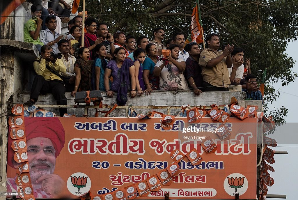 A banner showing BJP leader Narendra Modi is seen as residents listen to his speech after his landslide victory in elections on May 16, 2014 in Vadodara, India. Early indications from the Indian election results show Mr Modi's Bharatiya Janata Party was ahead in 277 of India's 543 constituencies where over 550 million votes were made, making it the largest election in history.