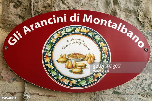 A banner showing Sicilian arancini for sale is seen close to the Montalbano's house on June 04 2018 in Punta Secca Ragusa Italy Inspector Salvo...