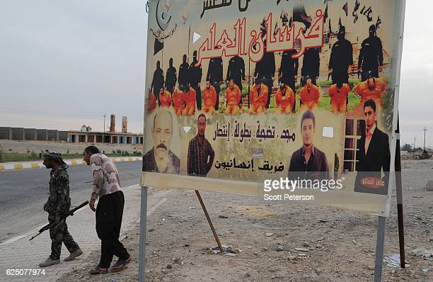A banner shows 11 men in orange jumpsuits executed by masked members of the Islamic State in December 2014 for defying ISIS rule at the Al Alam...