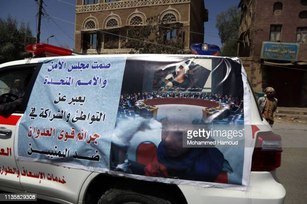 A banner shows words condemning the silence of the UN towards the killing of women and children by airstrikes carried out by the Saudiled coalition...