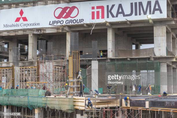 A banner stands above workers as they labor on a building at the under construction Meikarta project developed by Lippo Group in Bekasi Regency West...