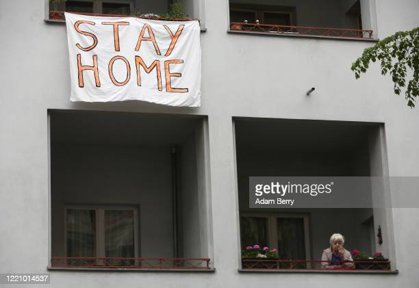 Banner telling protesters to stay home hangs out of a window as activists demonstrate against restrictions on public life designed to stem the spread...