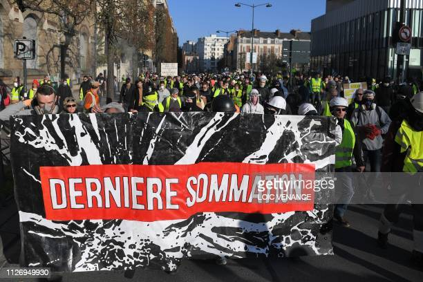 A banner that reads 'last warning' is carried as members of the yellow vest take part in the 15th consecutive Saturday of demonstrations in Rennes...