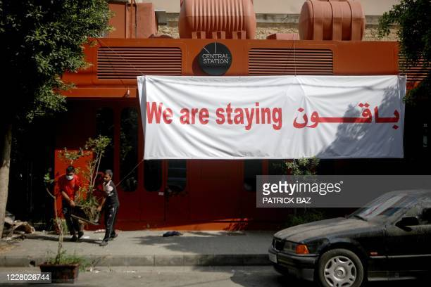 """Banner that reads """"We are staying"""" hangs on the front of a damaged shop in the partially destroyed Beirut neighbourhood of Mar Mikhael on August 13..."""
