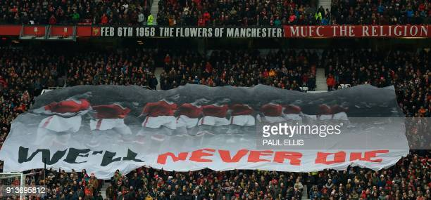 A banner that reads 'we'll never die' travels across the Stretford End in comemmoration of the 1958 Munich Air Disaster in the 60th anniversary year...