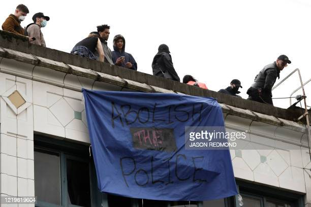 A banner which reads abolish the police hangs from a building in an area being called the Capitol Hill Autonomous Zone located on streets reopened to...