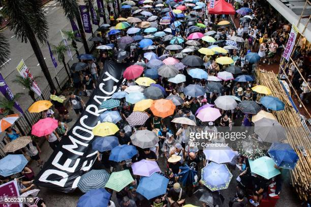 A banner which reads 'Democracy' is carried during a protest march in Hong Kong on July 1 coinciding with the 20th anniversary of the city's handover...