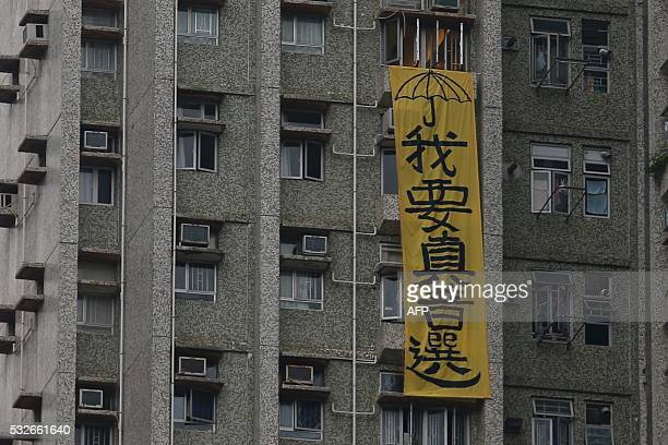 A banner which reads I need real universal suffrage is displayed outside a residential flat near an aged care complex where Zhang Dejiang the...