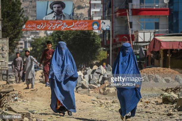 Banner with a picture of late Afghan commander Ahmad Shah Massoud is installed next to residential buildings as burqa-clad Afghan women walk along an...