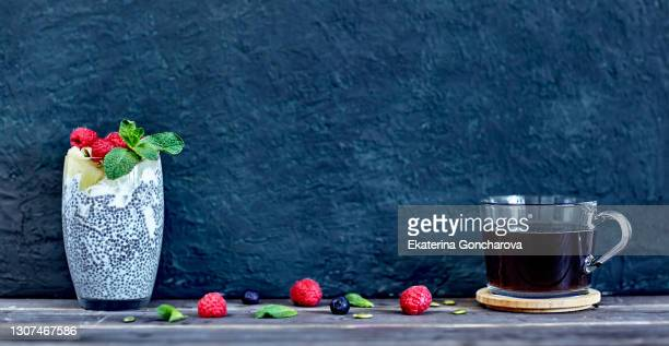 banner with beautiful chia pudding with raspberry, pineapple, blueberry and pumpkin seeds in a jar on wood table and blue background with coffee drink. - coffee drink stock pictures, royalty-free photos & images