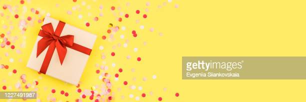 banner with gift box with confetti on yellow background. - gifts stock pictures, royalty-free photos & images