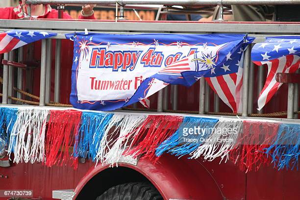 Banner With Text On Vehicle Trailer Over Street During Fourth Of July Parade