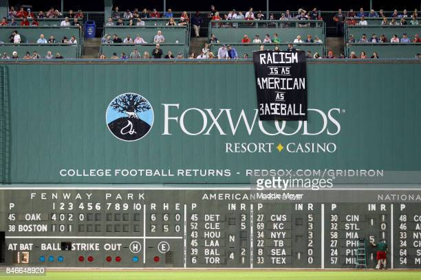 A banner with the message 'Racism is as American as baseball' is draped over the Green Monster by fans during the fourth inning of the game between...