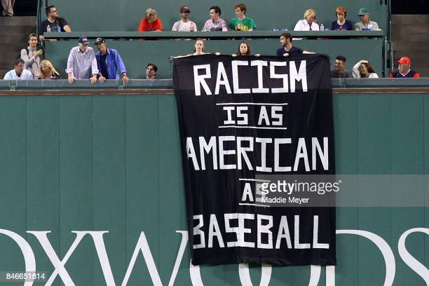A banner with the message 'Racism is as American as baseball' is draped over the Green Monster during the fourth inning of the game between the...