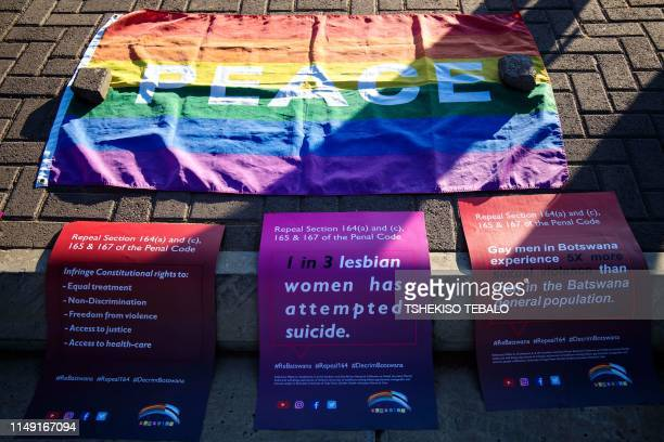 Banners and a rainbow flag are placed on the pavement outside the High Court in Gaborone on June 11 2019 Botswana's Court ruled on June 11 in favour...