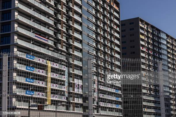 Banners and flags hang from apartments in the Tokyo Olympics athletes village on July 19, 2021 in Tokyo, Japan. Two South African football players...