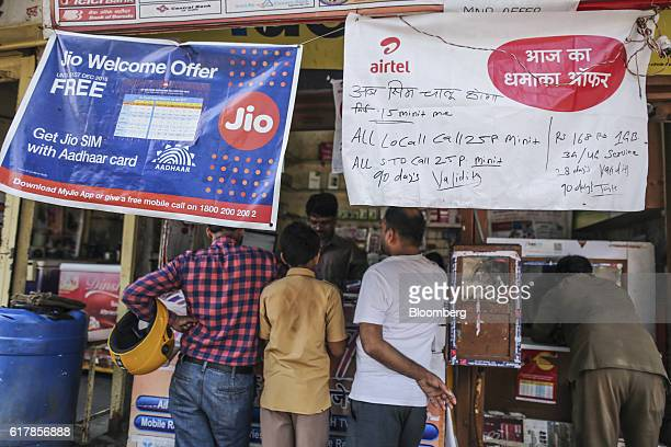 Banners for Reliance Jio the mobile network of Reliance Industries Ltd top left and Bharti Airtel Ltd hang outside a mobile phone store in Mumbai...