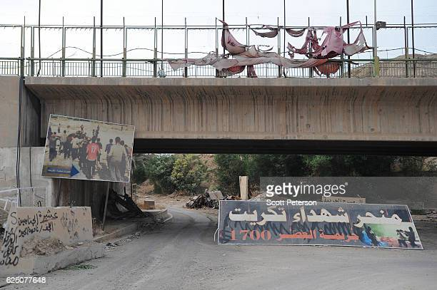 Banners mark the entrance to the memorial to the Islamic State massacre of 1,700 Shiite Air Force cadets from Camp Speicher beneath a bridge where...