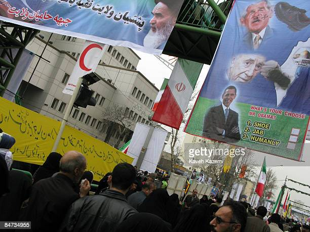 Banners of Ayatollah Khomeini alongside ones of George W Bush with a shoe hitting his face and questionnaire for Obama are posted on pedestrian...