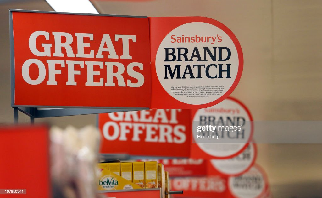Banners promoting Sainsbury's 'Brand Match' price campaign stand at the ends of product aisles inside a J Sainsbury Plc supermarket store in Godalming, U.K., on Thursday, May 2, 2013. J Sainsbury Plc, the U.K.'s third-largest supermarket chain, will report full year results on May 8. Photographer: Chris Ratcliffe/Bloomberg via Getty Images